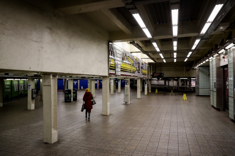 Image: A woman walks through the nearly empty Times Square subway station in New York on Thursday.