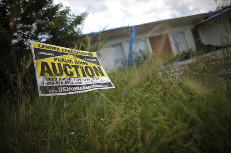 An auction sign for a property is seen at the front garden of a foreclosed house in Miami Gardens, Fla., in 2009.