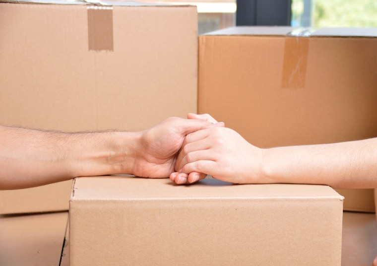 Image: a new beginning, Close up of a couple holding hands over a carton box and moving home