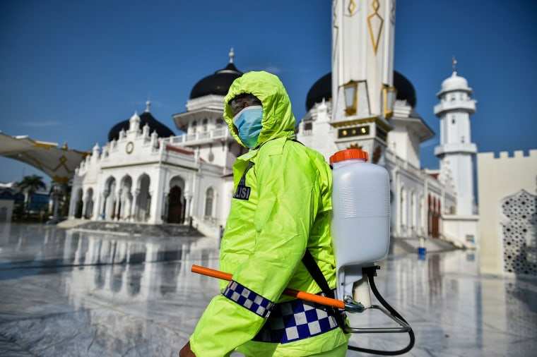 Image: An Indonesian police officer sprays disinfectant in the Baiturrahman grand mosque, amid concerns of the COVID-19 coronavirus, in Banda Aceh