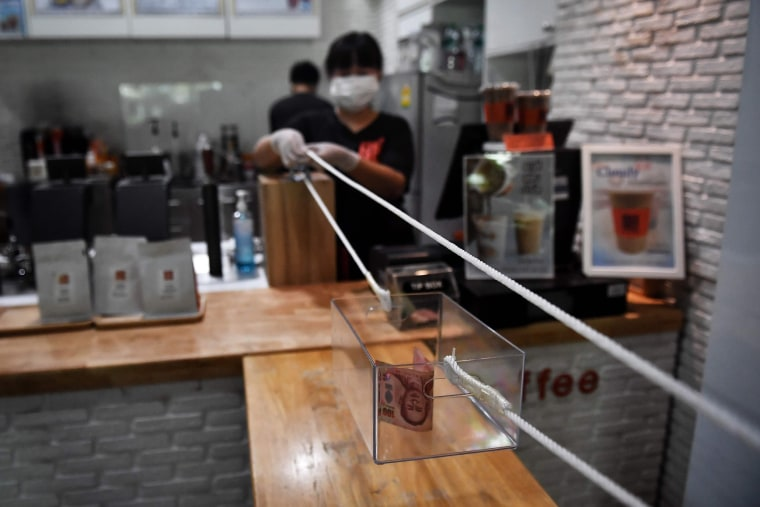 """Image: A barista from the """"Art Of Coffee"""" cafe uses a pulley system to accept cash for a cup of coffee from a customer, in an effort to practise social distancing amid concerns over the spread of the COVID-19 coronavirus, in Bangkok"""