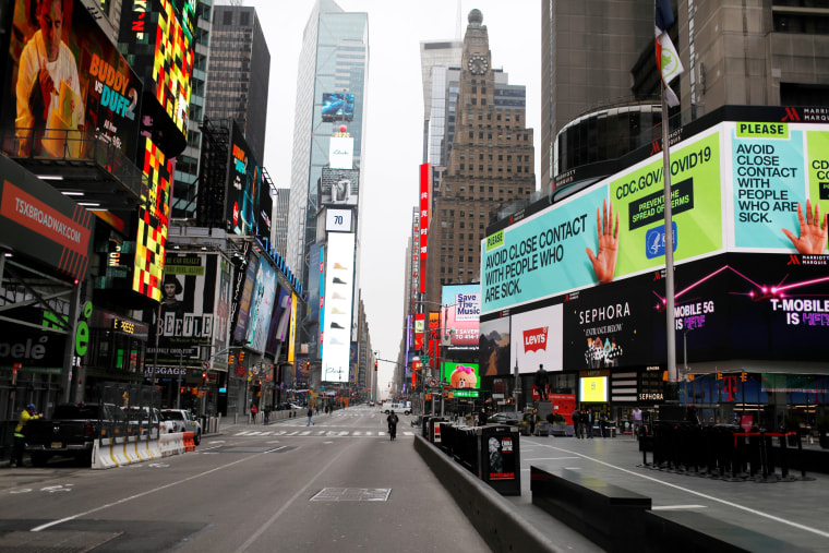 Image: A message about protecting yourself from the coronavirus disease (COVID-19) is seen on an electronic billboard in a nearly empty Times Square