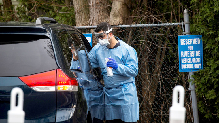 Image: Worker in protective clothing tests a person in a car at a testing center for coronavirus disease (COVID-19), at Riverside Medical Group in Secaucus, New Jersey
