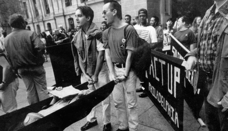 "Image: Chris Bartlett, left, and Dominic Piccirelli hold a stretcher carrying a fellow protester at an ACT UP ""die in"" protest outside Philadelphia's City Hall in 1990."