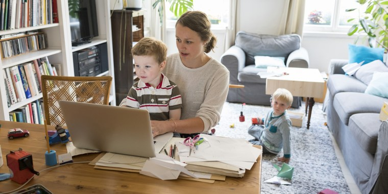 Female professional with two sons working at home