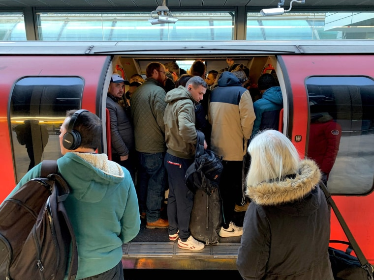 Image: Passengers squeeze on to a busy Central Line underground train at Stratford station, east London