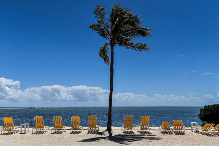 Image: Empty lounge chairs on a deserted beach at a resort in Windley Key, on March 22, 2020, during the coronavirus (COVID-19) outbreak.