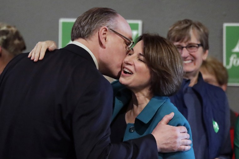 Sen. Amy Klobuchar, D-Minn., center, gets a kiss from her husband, John Bessler, upon arriving at a rally in Sioux City, Iowa, on Feb. 1, 2020.