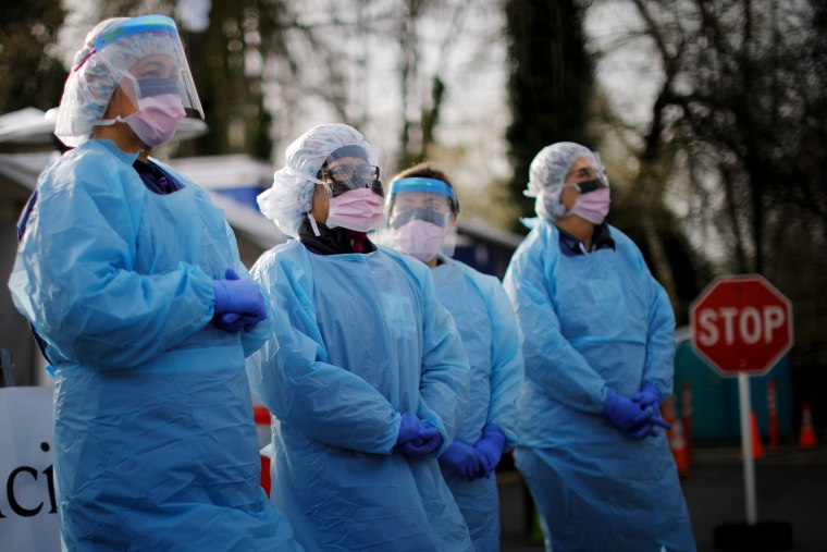 Image: Nurses wearing protective gear wait for patients at a drive-through coronavirus testing site in Seattle on March 17, 2020.