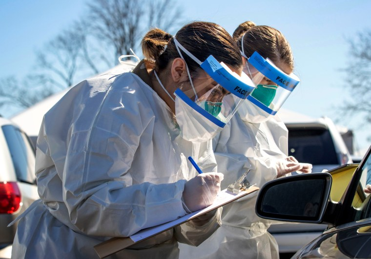 Image: Army Spc. Reagan Long and Pfc. Naomi Velez register people at a coronavirus mobile testing center in New Rochelle, N.Y., on March 14, 2020.