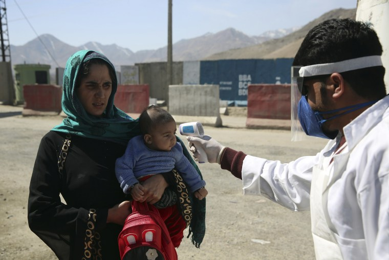 Image: An Afghan health worker measures the temperature of Afghan passengers in an effort to prevent the spread of the coronavirus, as they enter Kabul trough Kabul's western entrance gate, in the Paghman district of Kabul