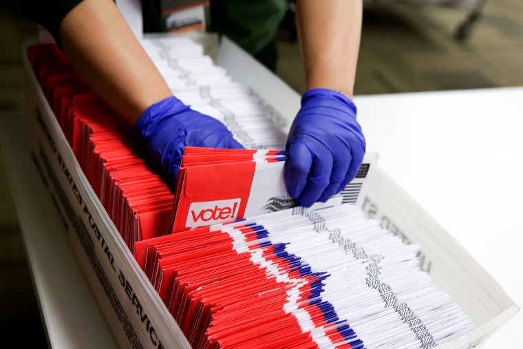 Image: A poll worker sorts vote-by-mail ballots in Renton, Wash., on March 10, 2020.