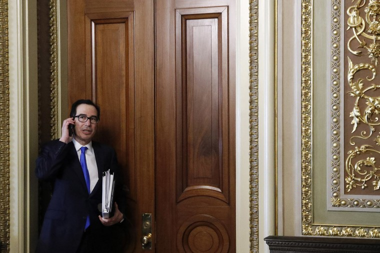 Image: Treasury Secretary Steve Mnuchin speaks on a phone after stepping out of a meeting on Capitol Hill