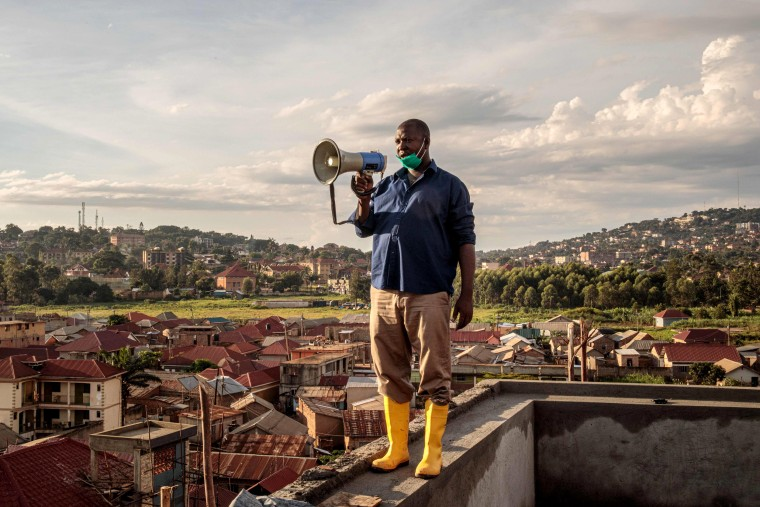 Image: Gonzaga Yiga, a community chairperson in the Ugandan capital of Kampala, speaks from the city's highest building to residents about the coronavirus on March 24, 2020.