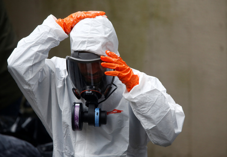 Image: A Servpro worker takes off protective gear after working on deep cleaning the Life Care Center of Kirkland,