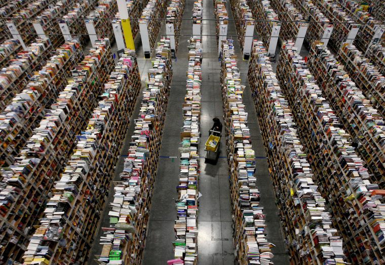 Worker gathers items for delivery at Amazon's distribution center in Phoenix.