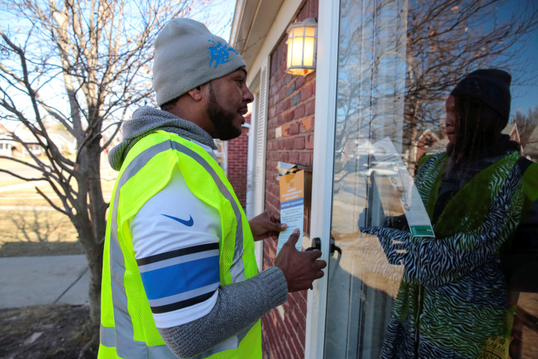 Image: Contract worker Vaughn Harrington delivers a notice by the Detroit Water and Sewerage Department to inform residents how to restore water service in response to the coronavirus outbreak in Detroit