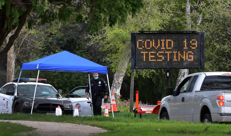 Image: A police officer mans the entrance to a coronavirus (COVID-19) testing center in Hansen Dam Park on March 25, 2020 in Pacoima, California.