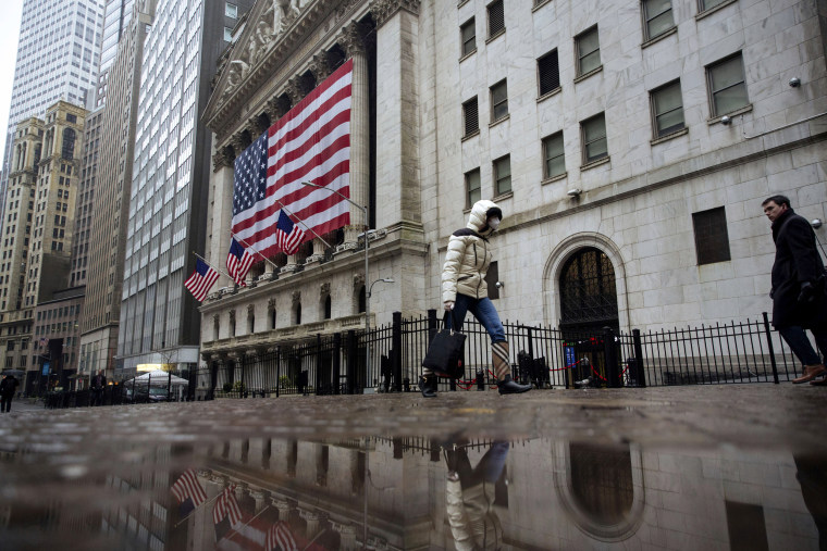 Image: A pedestrian wearing a masks walks past the New York Stock Exchange on March 19, 2020.
