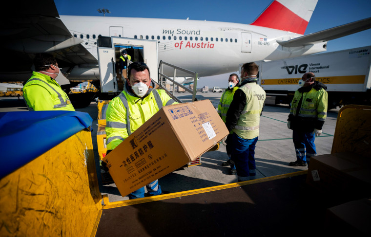 Image: Workers unload protective equipment bound for Italy that arrived from China at the Vienna Airport in Austria on March 23, 2020.