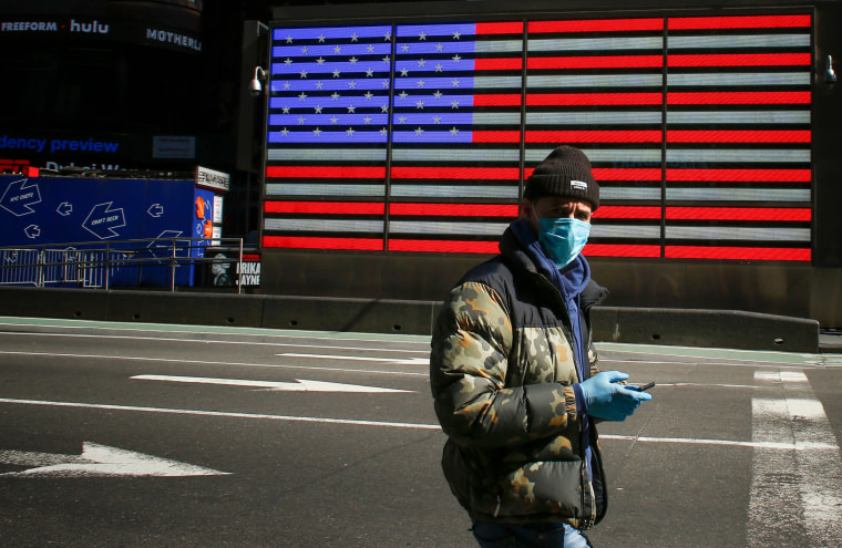 Image: A man wearing a mask checks his phone in Times Square in New York on March 22, 2020.