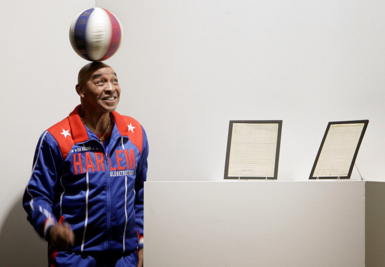 Image: Former Harlem Globetrotter Curly Neal spins a ball on his head at Sotheby's in New York in 2010.