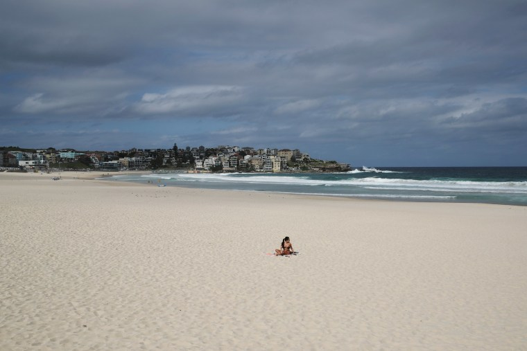 Image: A single sunbather remains following the closure of Bondi Beach to prevent the spread of the coronavirus disease (COVID-19) in Sydney
