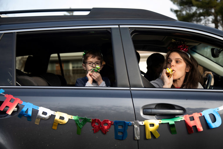 Image: Family and friends line up down the street to wish for a birthday celebration drive-by