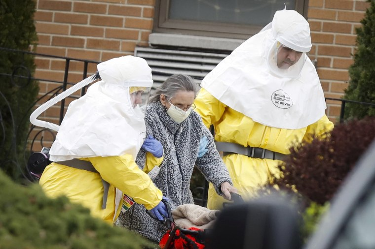 Image: Medical officials aid a residents from St. Joseph's nursing home to board a bus, after a number of residents tested positive for coronavirus disease (COVID-19) in Woodbridge, New Jersey