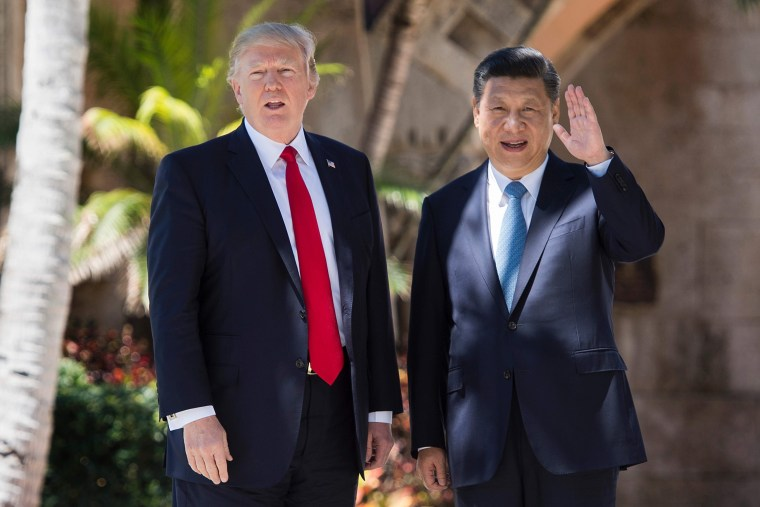 Image: Chinese President Xi Jinping waves to the press as he walks with President Donald Trump at the Mar-a-Lago estate in West Palm Beach, Florida, April 7, 2017.