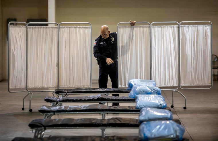 Image: A health public information officer looks at beds at a temporary hospital set up by the California National Guard in Indio on March 29, 2020.