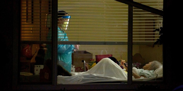 A healthcare worker attends to Susan Hailey, who tested positive for coronavirus, at the Life Care Center of Kirkland in Washington state on March 13, 2020.