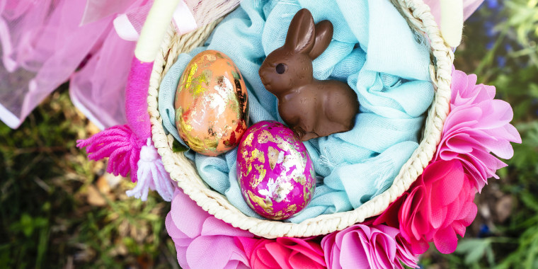 Overhead view of girl with Easter eggs and bunny in basket