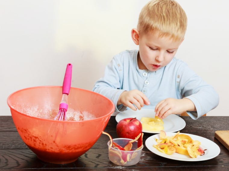 Young boy cooking with peeled apples