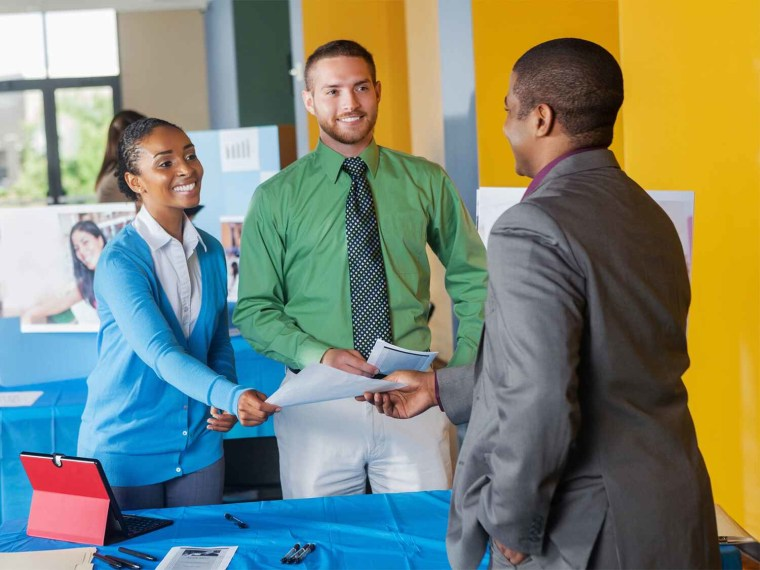 Three adults exchange paper at a college fair