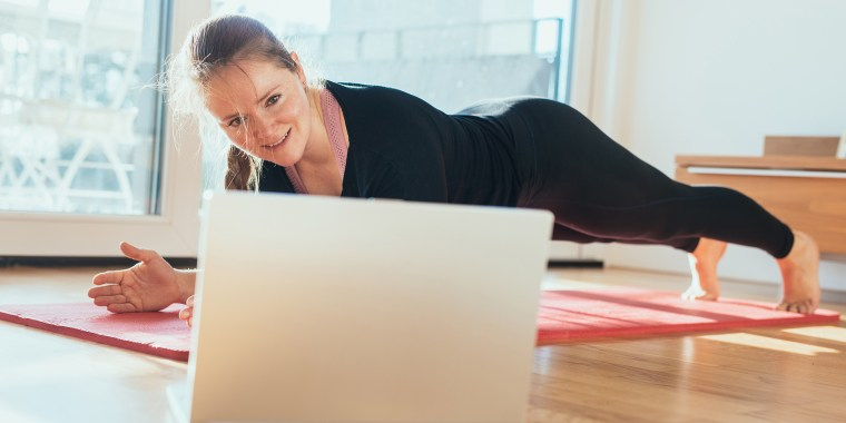 Woman doing sport in front of laptop at home.