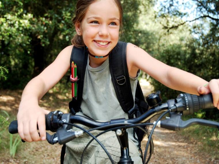 Tween girl in green dress with backpack biking through the woods