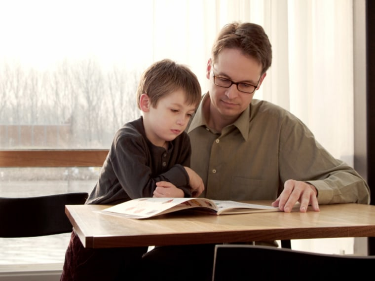 Father reading book to young son