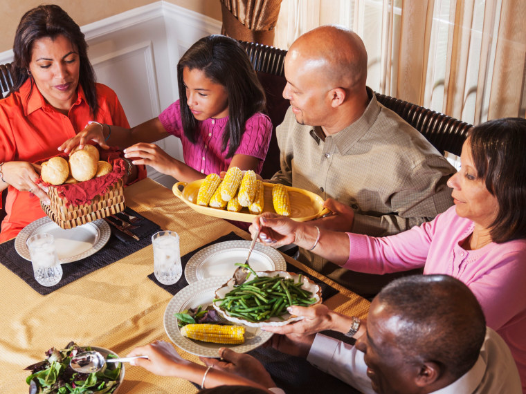 Family of five with daughter, mom, dad, and grandparents passing bread and corn for dinner at the table