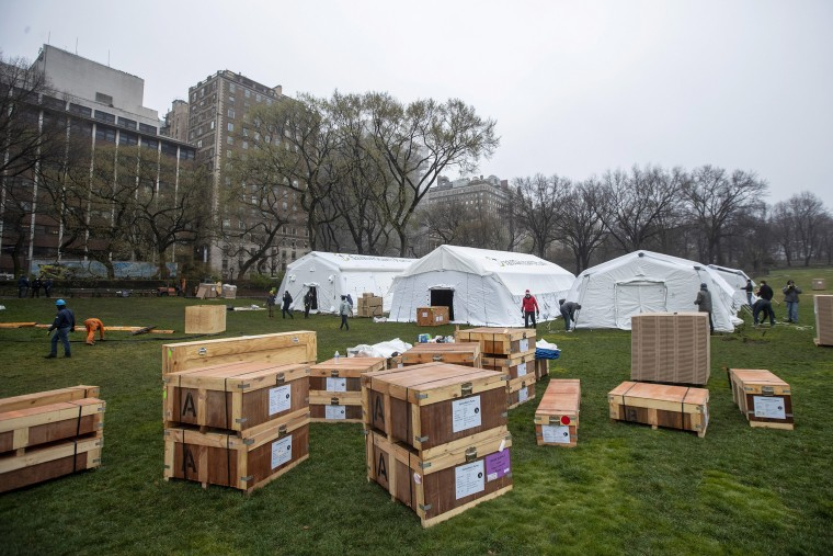 Image: A Samaritan's Purse crew works on building an emergency field hospital equipped with a respiratory unit in New York's Central Park across from the Mount Sinai Hospital