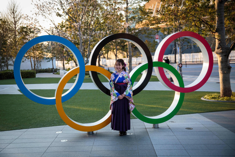 Image: A woman wearing a traditional Japanese kimono poses next to the Olympic rings in front of the Japan National Stadium, the main venue for the Tokyo 2020 Olympic Games, in Tokyo.