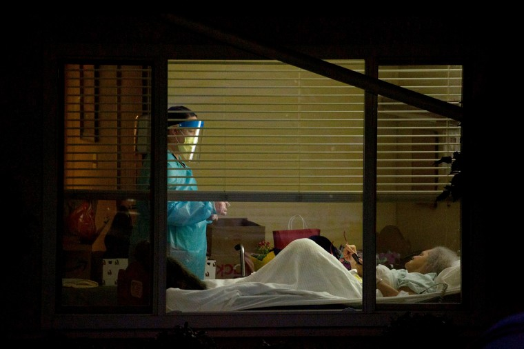 Image: A healthcare worker attends to Susan Hailey, who tested positive for coronavirus, at the Life Care Center of Kirkland in Washington state on March 13, 2020.