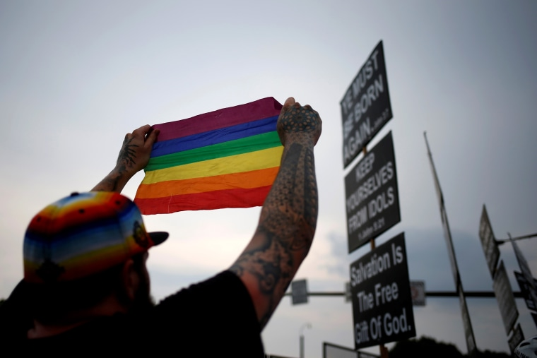 Image: A man holds up a pride flag towards members of the Westboro Baptist Church as they protest at the Democratic National Convention in Philadelphia in 2016.
