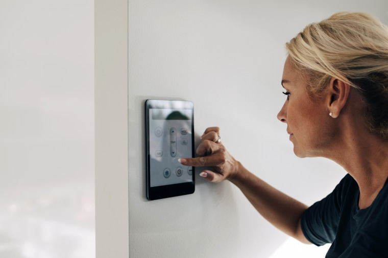 Image: Blond woman adjusting thermostat using digital tablet mounted on white wall at home