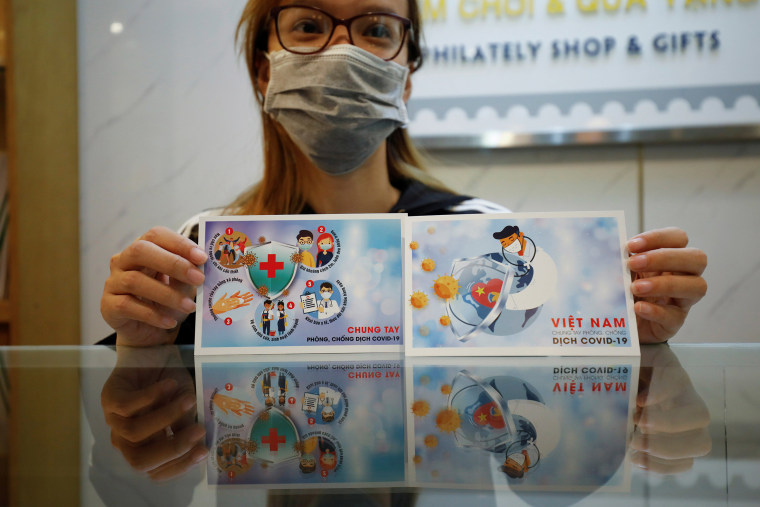 Image: A stamp seller shows off special postcards with anti-coronavirus images in Hanoi, Vietnam March 31, 2020.