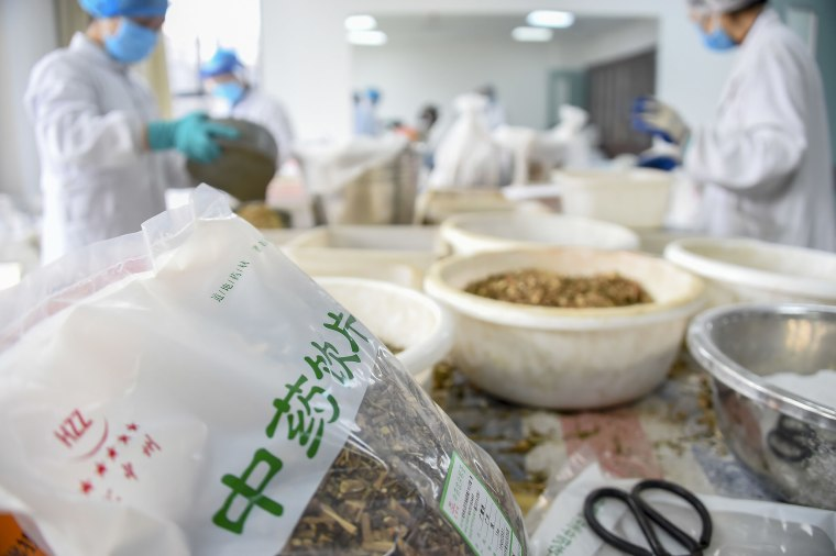 Image: Traditional Chinese medicine pharmacists prepare herbs to produce doses of TCM concoctions to help combat the novel coronavirus epidemic at Xiaogan Chinese Medical Hospital in Xiaogan City, central China's Hubei Province