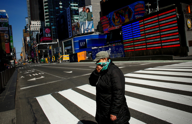 Image: A woman crosses through Times Square as she covers her face on March 22, 2020.