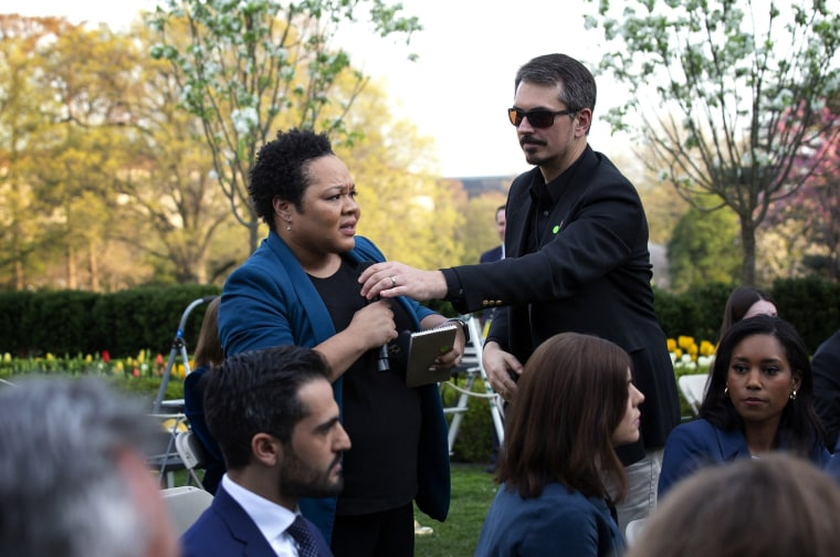 Image: A White House aide attempts to take the microphone from reporter Yamiche Alcindor as she asks President Donald Trump a question at a coronavirus press conference on March 29, 2020.