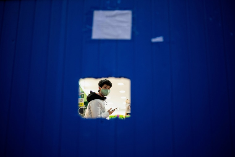 Image: A store workerwearing a wearing a facemask as a preventive measure against the COVID-19 coronavirus waits for costumers behind a barrier in Wuhan