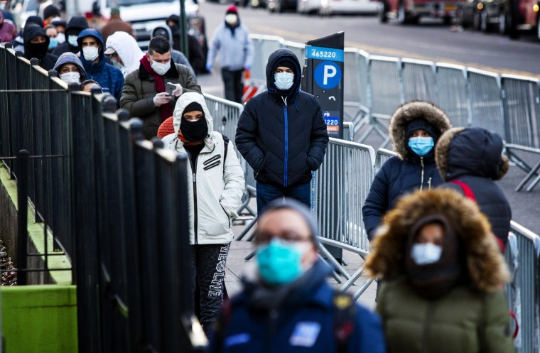 Image: People line up to get a coronavirus test at Elmhurst Hospital in Queens, N.Y., on March 24, 2020.